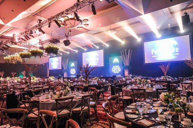 Festive event hall for a gala dinner, illuminated stage, LED screens