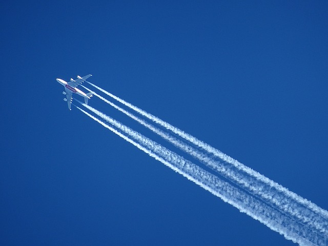 Buttom view of airplane with contrails in the dark blue sky
