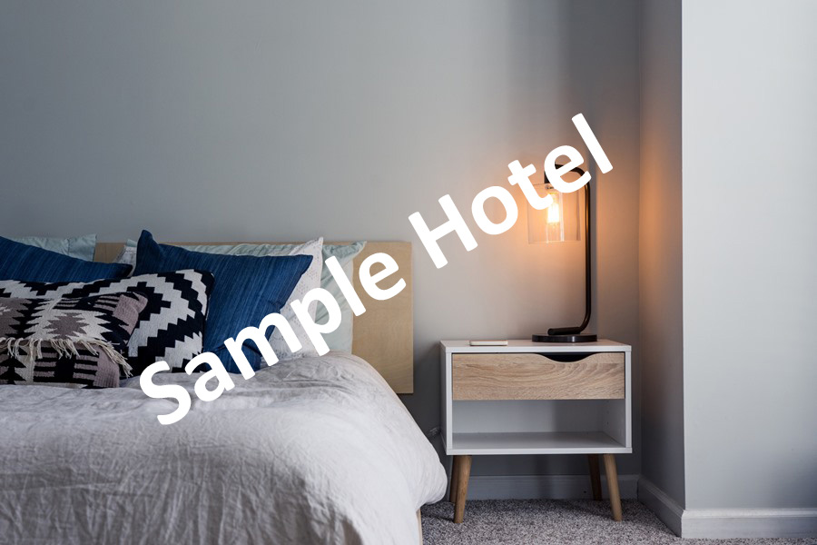 Sample hotel room, bed, wooden beside table and lamp