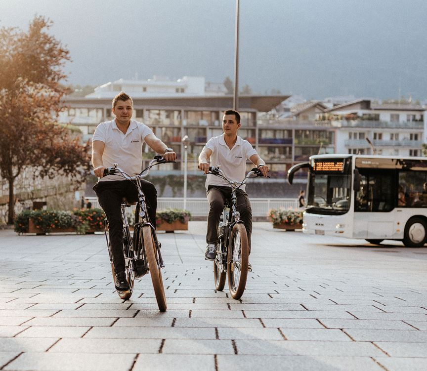 Two young men with e-bikes, apartments and bus in the back
