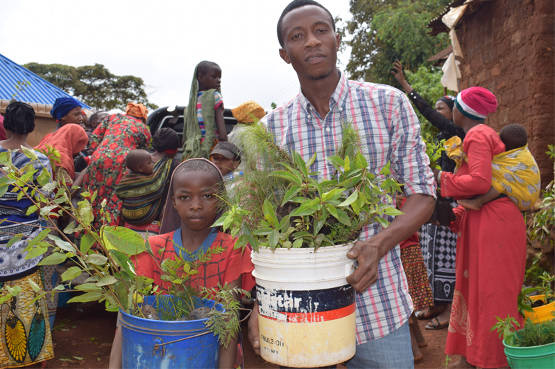 Young African man with young boy holding tree seedlings in their hands, more people in the back